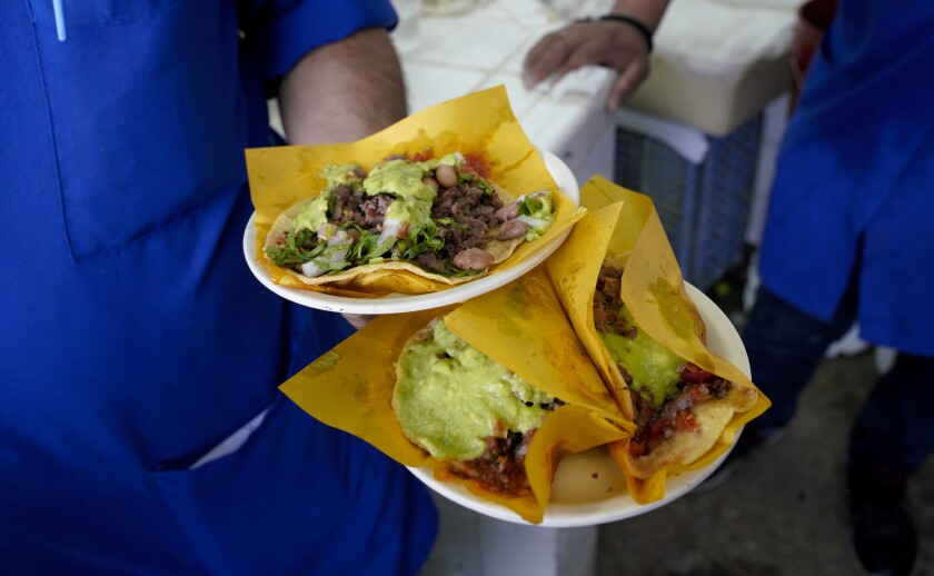 At the popular Taqueria Franc in Tijuana, Mexico on August 6, 2019, a waiter carries an assortment of carne asada and al pastor tacos to customers in the dining room.
