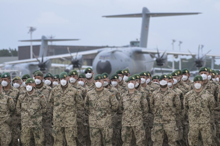 Soldiers of the German Armed Forces have lined up in front of the Airbus A400M transport aircraft of the German Air Force for the final roll call in Wunstorf, Germany, Wednesdat, June 390, 2021. The last soldiers of the German Afghanistan mission have arrived at the air base in Lower Saxony. The mission had ended the previous evening after almost 20 years. The soldiers had been flown out with four military planes from the field camp in Masar-i-Sharif in the north of Afghanistan. (Hauke-Christian Dittrich/Pool via AP)
