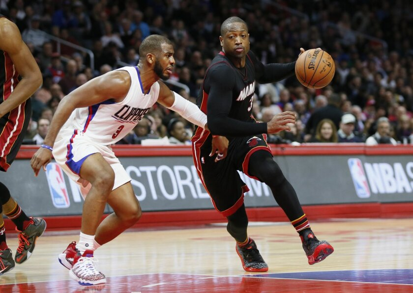 FILE - In this Wednesday, Jan. 13, 2016 file photo, Miami Heat's Dwyane Wade, right, dribbles the ball while Los Angeles Clippers' Chris Paul, left, defends him during the second half of an NBA basketball game in Los Angeles. (AP Photo/Danny Moloshok, File)