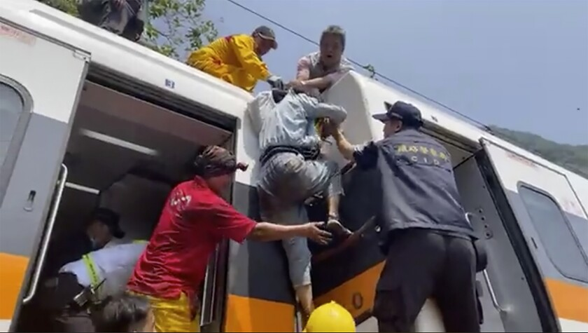 A passenger is helped out of a derailed train