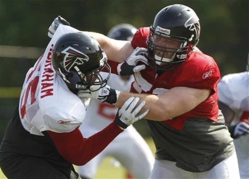 Atlanta Falcons offensive tackle Sam Baker, right, blocks defensive end John Abraham (55) during their NFL football training camp workout in Flowery Branch, Ga., Monday, Aug. 1, 2011. (AP Photo/John Bazemore)