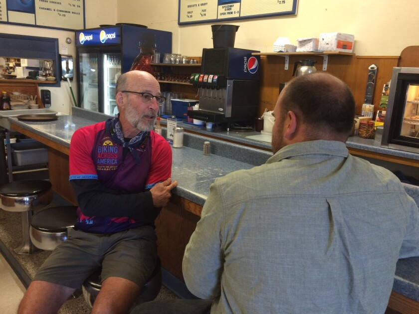 Dr. Paul Gordon talks with a 28-year-old railroad worker at the Speedway Diner in Forsyth, Mont., during his summer-long bike trip devoted to talking to Americans about Obamacare.