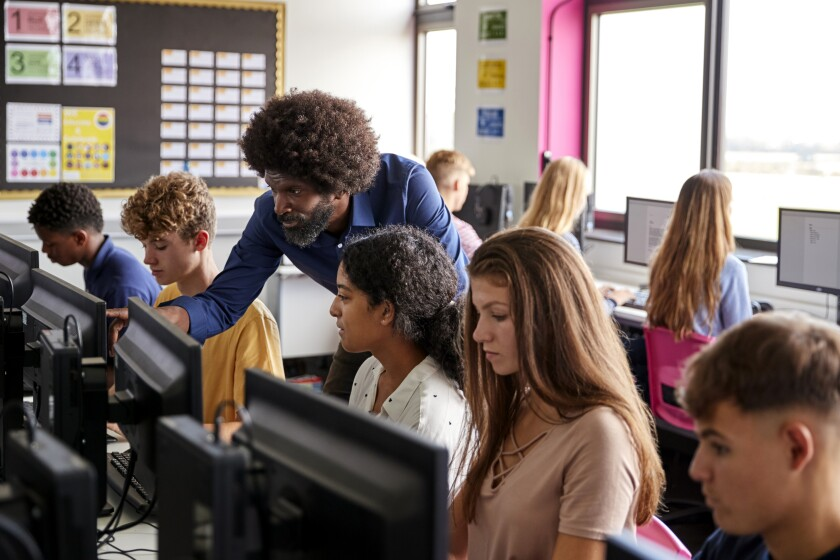 A teacher in a computer class helps one of the students.
