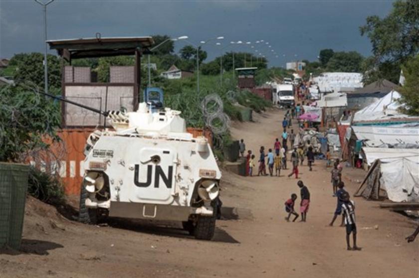 """ARCHIVO - En esta fotografía de archivo del, algunos de los más de 30.000 civiles refugiados en una base de las Naciones Unidas en Yuba, capital de Sudán del Sur, caminan junto a un vehículo blindado y una torre de vigilancia operados por cascos azules chinos. La ONU comenzará a proporcionarles a sus fuerzas de paz tarjetas de """"sin excusas"""", parte de un esfuerzo más amplio para combatir los abusos sexuales en los operativos de estabilización internacional efectuados por el organismo. (AP Foto/Jason Patinkin, archivo)"""