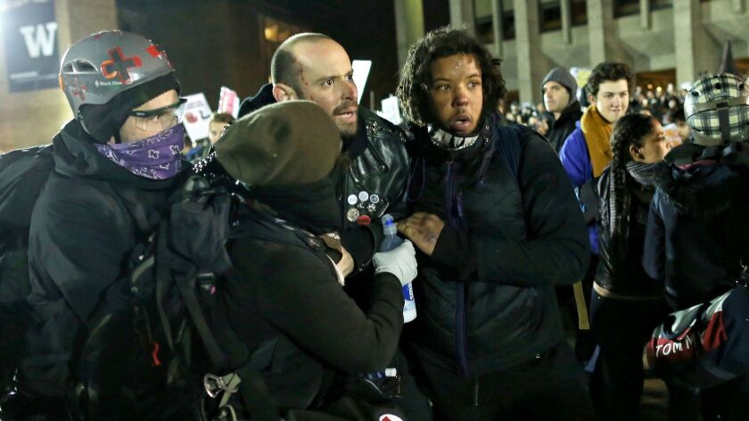 A man wounded by gunshot is assisted at a protest at the University of Washington in Seattle against an appearance by Breitbart editor Milo Yiannopoulos.