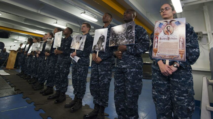 In this 2013 file photo, sailors hold photos of civil-rights activists, armed-services veterans and significant people and events during a Black History Month celebration in the forecastle aboard the Nimitz-class aircraft carrier USS Carl Vinson (CVN 70).
