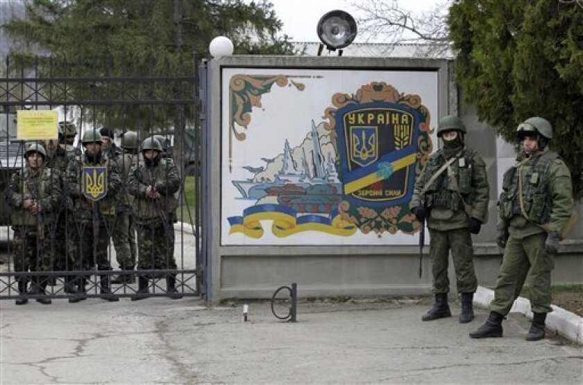 Ukrainian soldiers, left, and unidentified gunmen gather at the gate of an infantry base in Privolnoye, in the Crimean region. Hundreds of the unidentified gunmen have arrived outside the base with vehicles that bear Russian license plates. The vehicles have surrounded the base and reportedly are blocking Ukrainian soldiers from entering or leaving.