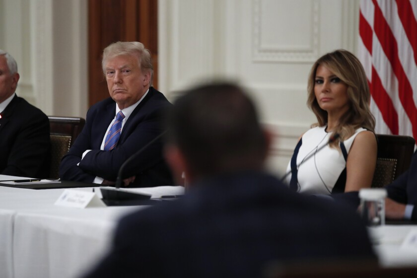 President Trump and First Lady Melania Trump listen during a meeting