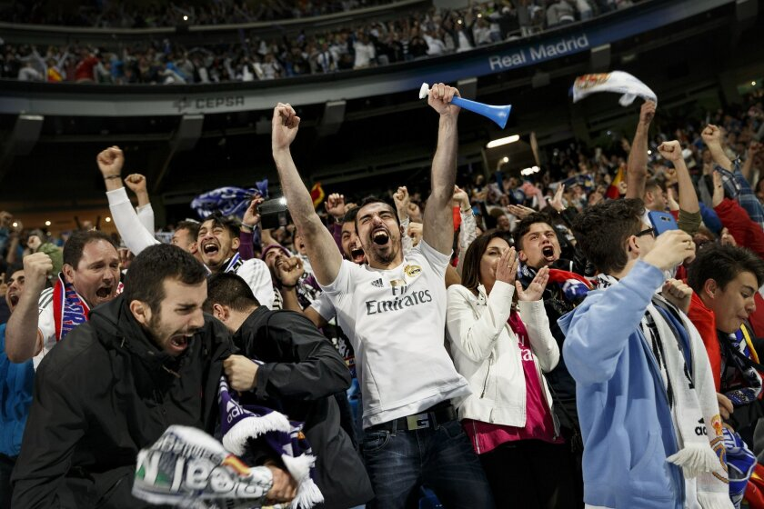 Real Madrid supporters react after their team won the Champions League final against Atletico Madrid while watching the game in Milan, Italy, on a giant screen at the Santiago Bernabeu Stadium in Madrid, Saturday, May 28, 2016. (AP Photo/Daniel Ochoa de Olza)