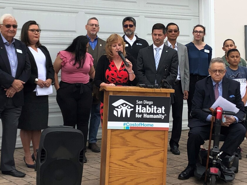 San Diego Habitat for Humanity President and CEO Lori Holt Pfeiler, at podium, as joing by elected officials and housing advocates Monday to announce her organization's support of a national campaign to help create affordable housing for 10 million people nationwide within five years.