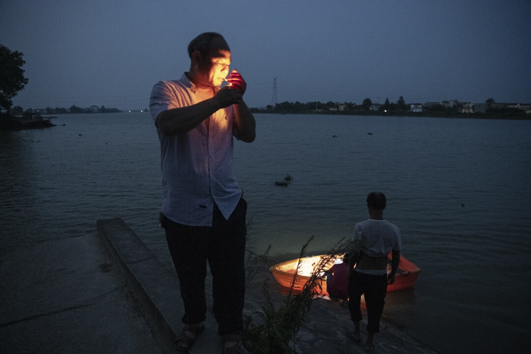 Huang Guoxin lights a cigarette near his home in Dixi village, Jiangxi province.