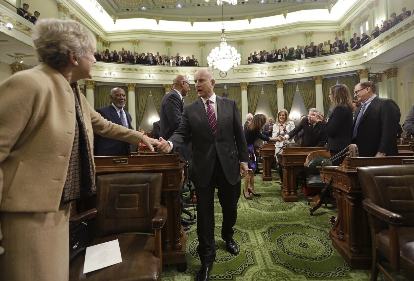 Gov. Jerry Brown, center, is greeted by lawmakers on the floor of the state Assembly before his inauguration at the state Capitol on Monday.