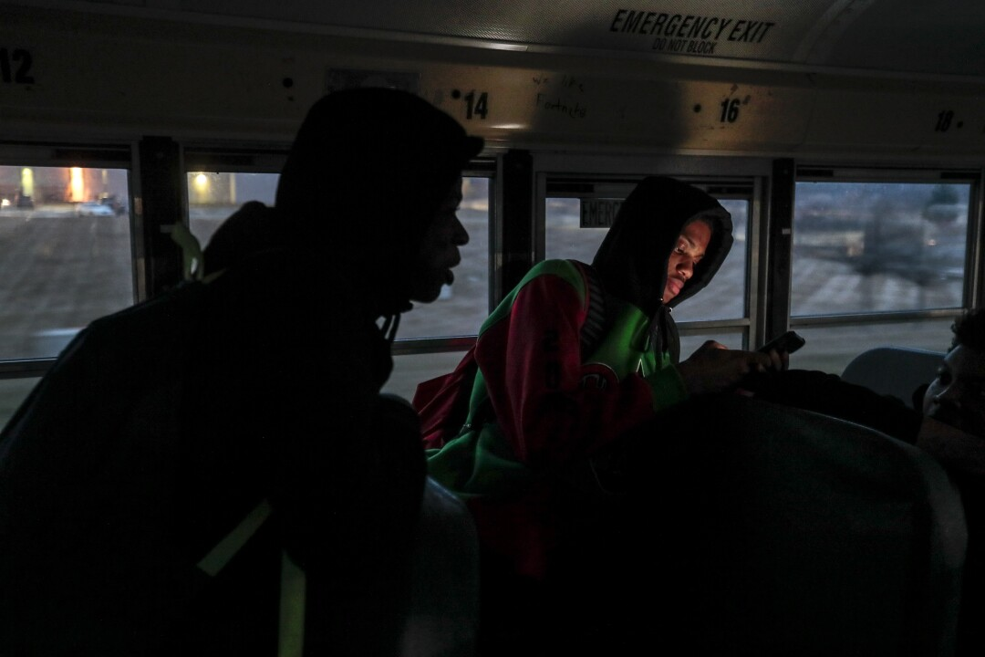 Dekobe Lemon checks his phone as the team rides the bus back to Flint after beating Davison.