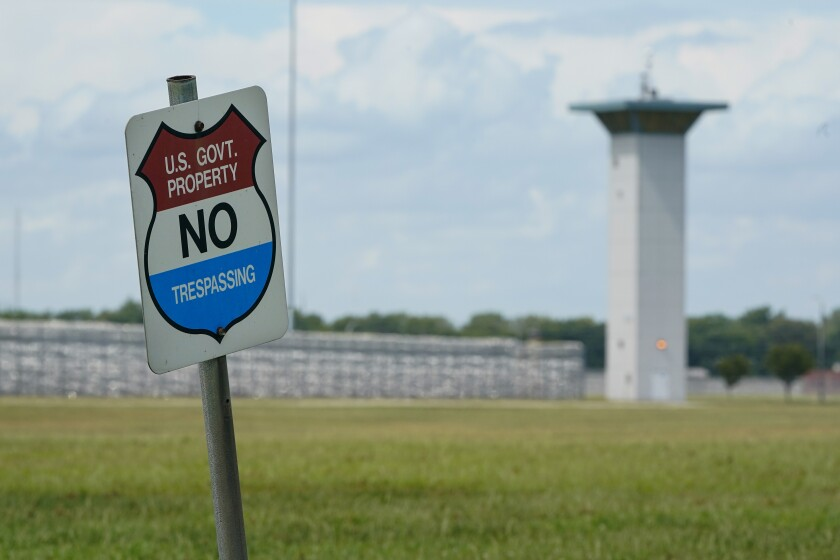 In this Aug. 28, 2020, file photo, a no trespassing sign is displayed outside the federal prison complex in Terre Haute, Ind. As Donald Trump's presidency winds down, his administration is throttling up the pace of federal executions despite a surge of COVID-19 cases in prison, announcing plans for five executions just days before the Jan. 20 inauguration of death penalty foe Joe Biden. Attorney General William Barr defends the action in an interview with The Associated Press and says he will likely schedule additional executions before leaving the Cabinet. (AP Photo/Michael Conroy, File)