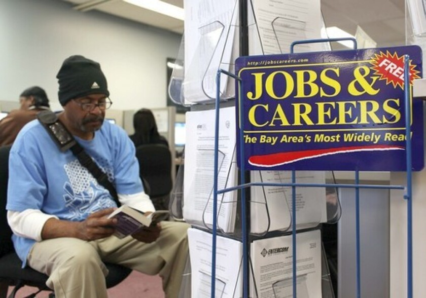 A job seeker waits to use a phone at a career center in Richmond, Calif.