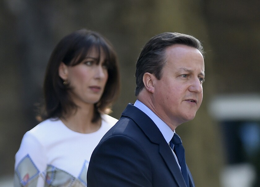Britain's Prime Minister David Cameron speaks outside 10 Downing Street as his wife Samantha looks on Friday.
