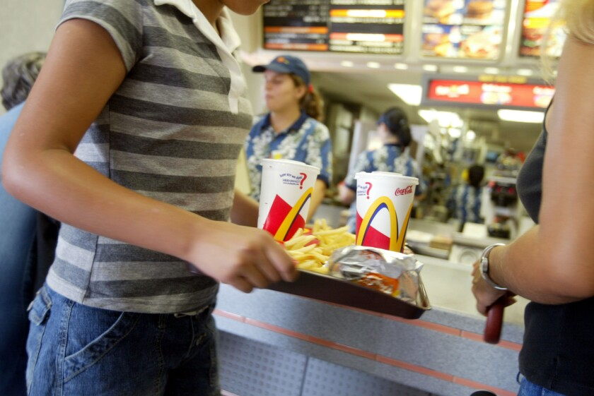 A customer carries a tray of food at McDonald's.