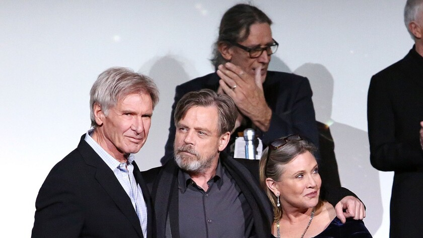 """Harrison Ford, Mark Hamill, Carrie Fisher and Peter Mayhew (background) attend the Hollywood premiere of """"Star Wars: The Force Awakens."""""""