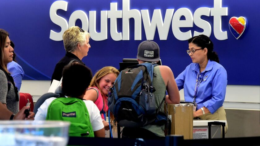 Travelers ask about their flights at a Southwest Airlines counter at Los Angeles International Airport. A fee to board early has been raised from $30 and $40 to $50 at certain airports.
