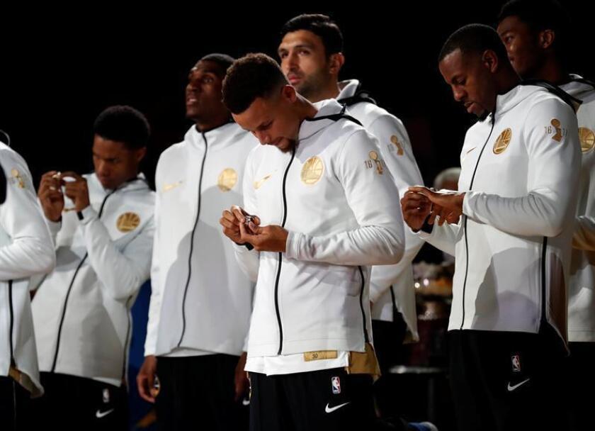 Los jugadores de los Golden State Warriors Stephen Curry (c), Andre Iguodala (d) y Patrick McCaw (i) observan sus anillos de campeones de la NBA. EFE/Archivo