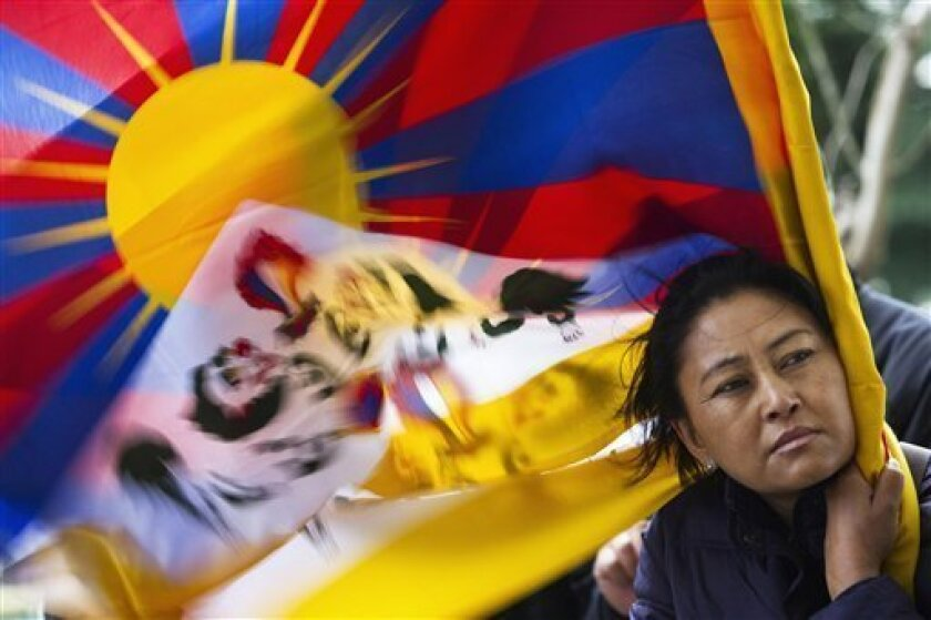 A Tibetan exhile holds a Tibetan flag in Dharmsala, India, as they mark the anniversary of a failed 1959 uprising against Chinese rule, Sunday, March 10, 2013. Police in India prevented a Tibetan man from setting himself on fire as hundreds of Tibetan exiles gathered to mark the anniversary in Dharmsala, the home of Tibet's government in exile. (AP Photo/ Ashwini Bhatia)