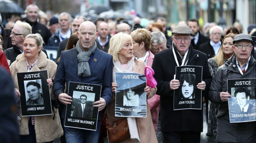 Families hold photographs of the victims of Bloody Sunday and march through the Bogside in Londonder