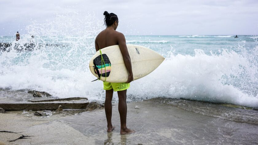 Ikaika Kailiawaa, 28, of Honolulu, finished surfing for the day and watched storm surge waves crash up on Waikiki Beach on Friday.