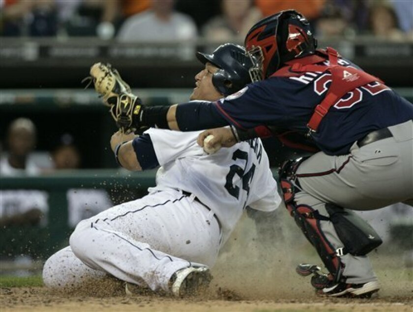 Detroit Tigers' Miguel Cabrera, left, looks up for the call after being tagged out by Minnesota Twins catcher Rene Rivera, right, while trying to score on a hit by Victor Martinez in the fifth inning of a baseball game Tuesday, May 31, 2011 in Detroit. The Tigers scored six runs in the fifth inning to take a 6-3 lead over the Twins. (AP Photo/Duane Burleson)