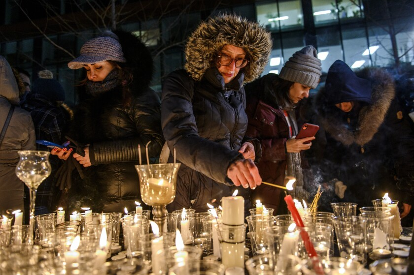"Members of Montreal's Iranian community attend a vigil, Thursday, Jan. 9, 2019 in downtown Montreal. It is ""highly likely"" that Iran shot down the civilian Ukrainian jetliner that crashed near Tehran late Tuesday, killing all 176 people on board, U.S., Canadian and British officials declared Thursday. They said the fiery missile strike could well have been a mistake amid rocket launches and high tension throughout the region. (Andrej Ivanov/The Canadian Press via AP)"