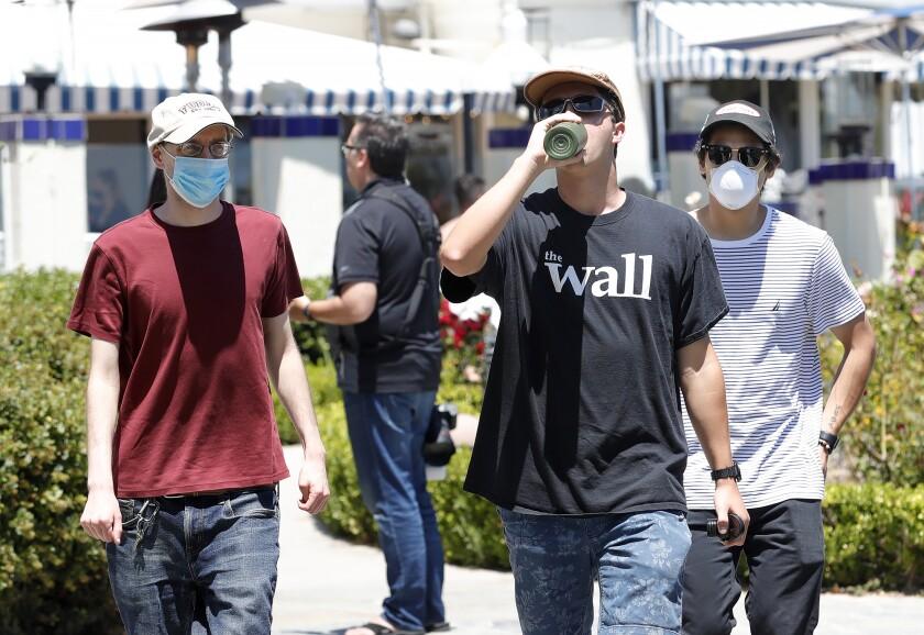 Teenagers walk the path near Heisler Park in Laguna Beach on July 16.