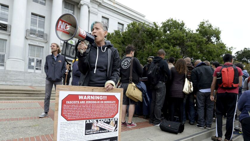 A protester uses a bullhorn to make her feelings known during a news conference held by the Berkeley College Republicans in Sproul Plaza on the UC Berkeley campus. The event was held to discuss last year's cancellation of speaker Ann Coulter's appearance on campus.