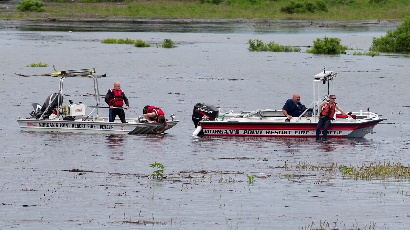 Morgan's Point Resort Fire Department rescue workers comb Lake Belton on Thursday at Owl Creek Park near Gatesville, Texas. Ft. Hood says nine soldiers were killed when an Army truck overturned in a rain-swollen creek.
