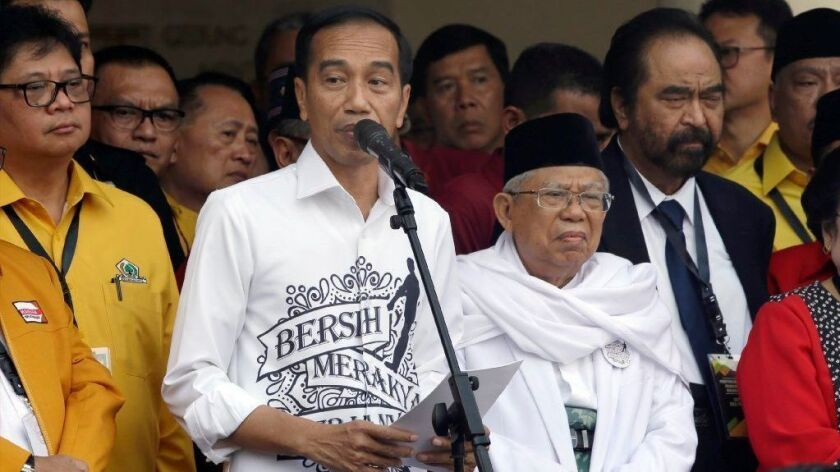 Indonesian President Joko Widodo, center left, speaks alongside his running mate, Ma'ruf Amin, center right, prior to registering as candidates for the 2019 election.