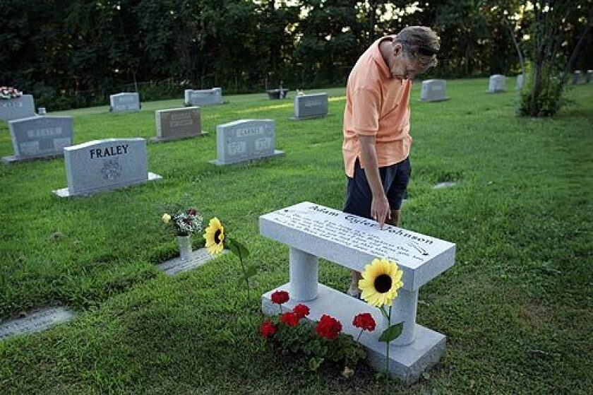 "Teddy Johnson traces his fingers along his son's name at his grave site. Adam, a college student and musician, died of a black-tar overdose, and his father found the young man's body. ""I had no clue,"" Teddy Johnson said. ""We're a small town. We weren't prepared."""