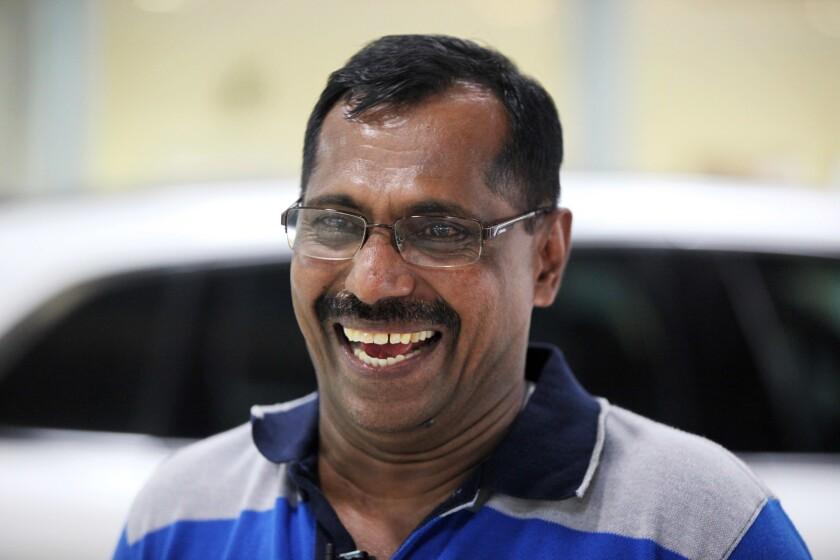 Mohamed Basheer, coordinador de operaciones al por mayor en un taller de hojalatería y pintura en un concesionario de autos de Dubai, ríe durante una entrevista en Dubai, Emiratos Arabes Unidos, el miércoles 10 de agosto del 2016. (AP Foto/Jon Gambrell)
