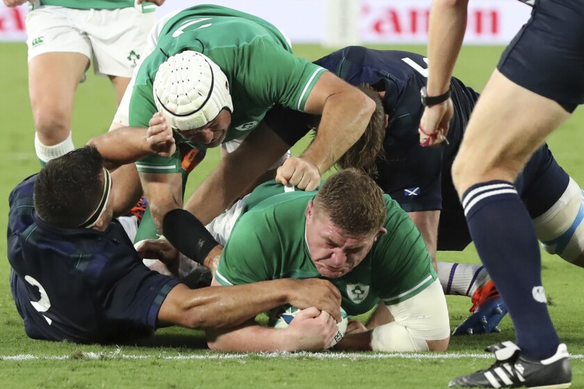 Ireland's Tadhg Furlong, center, carries a ball to score the teams' third try during the Rugby World Cup Pool A game at International Stadium between Ireland and Scotland in Yokohama, Japan, Sunday, Sept. 22, 2019. (AP Photo/Eugene Hoshiko)