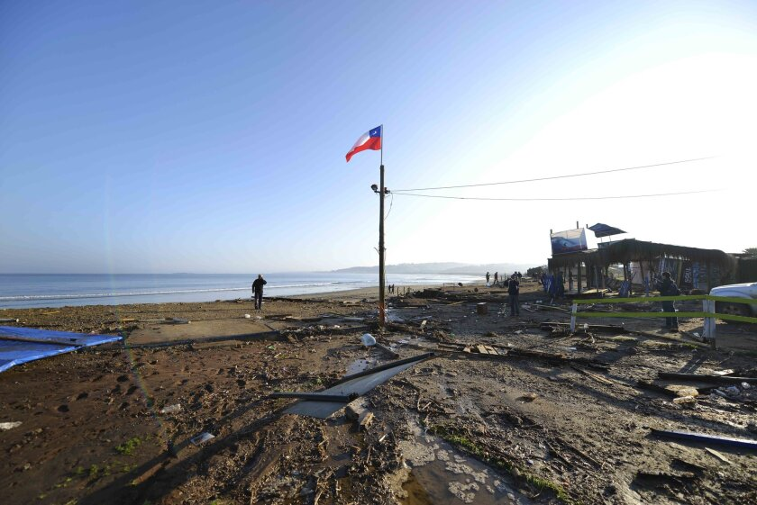 A man walks past a lone Chilean flag where surfing schools once stood, swept away by an earthquake-triggered tsunami in Concon, Chile.