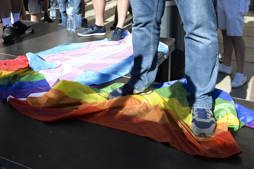 FILE - In this Sunday, Aug. 16, 2020 file photo, a man stands on a Rainbow Flag as he attends a demonstration of far-right activists against LGBT rights in Warsaw, Poland. A rural region in southern Poland has revoked an anti-LGBT resolution under the threat of losing European Union funding. The regional assembly of Swietokrzyskie voted in a special session on Wednesday, Sept. 22, 2021 to revoke the resolution, first passed in 2019. (AP Photo/Czarek Sokolowski, file)