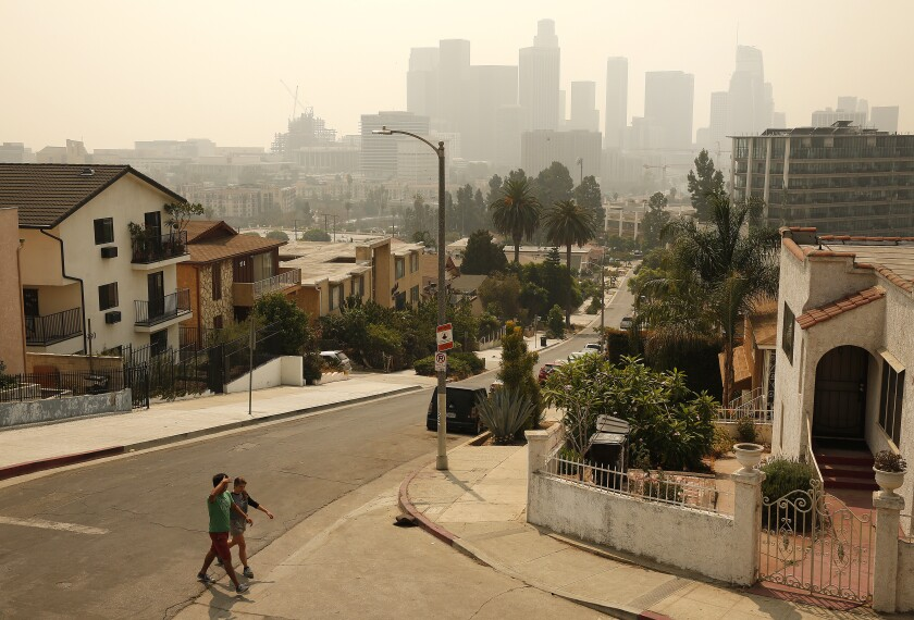 Alli Coyler and Luis Garcia walk under smoky skies along Figueroa Terrace near downtown L.A. on Monday.