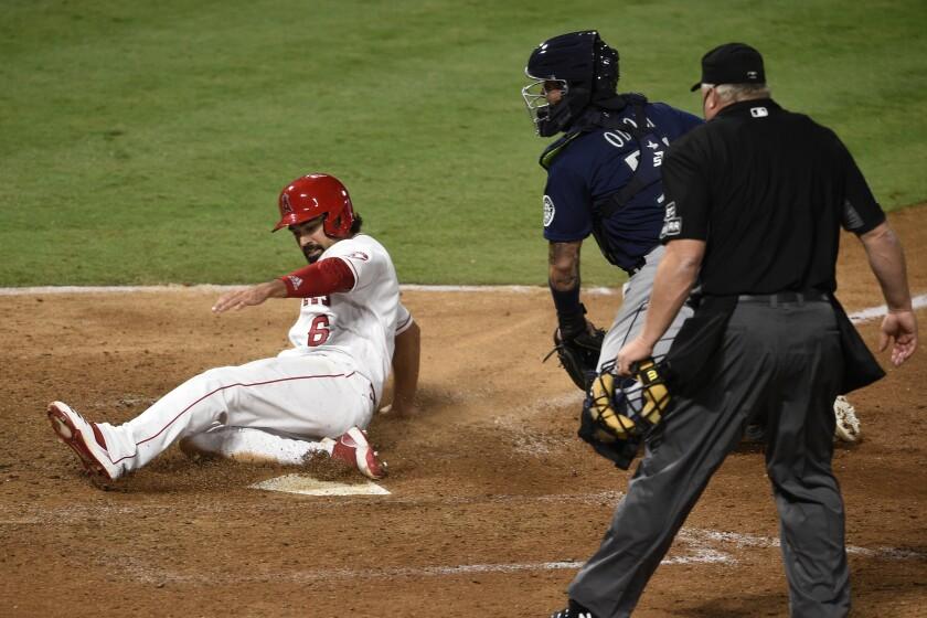 Angels third baseman Anthony Rendon, left, slides into home past Seattle Mariners catcher Joseph Odom.