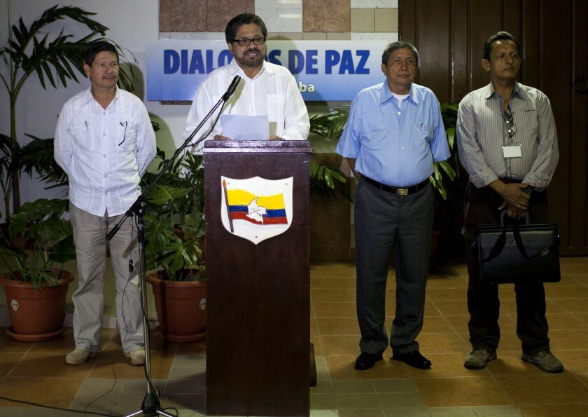 FILE - In this Feb. 28, 2014 file photo, Ivan Marquez, chief negotiator for the Revolutionary Armed Forces of Colombia, or FARC, center, speaks to journalists accompanied by Commander Fabian Ramirez, left, and Commanders Jairo Martinez, second from right and Fidel Rondon, during the continuation of peace talks with Colombia's government in Havana, Cuba. The FARC issued a statement issued Wednesday, May 27, 2015 that said the man known by the alias Jairo Martinez was among 27 rebel fighters killed during an attack on a guerrilla camp in southwest Colombia last week. The FARC says Martinez was visiting troops to discuss progress at the peace talks when they were surprised by the air and ground assault. Martinez's real name is Pedro Nel Daza. (AP Photo/Franklin Reyes, File)