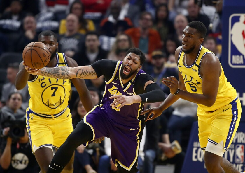 Lakers star Anthony Davis is fouled by Golden State Warriors center Kevon Looney during the Lakers' 116-86 victory Thursday.