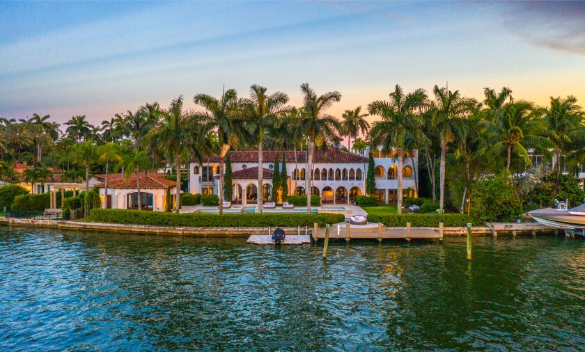 The three-story mansion spans 11,460 square feet and boasts 158 feet of water frontage.