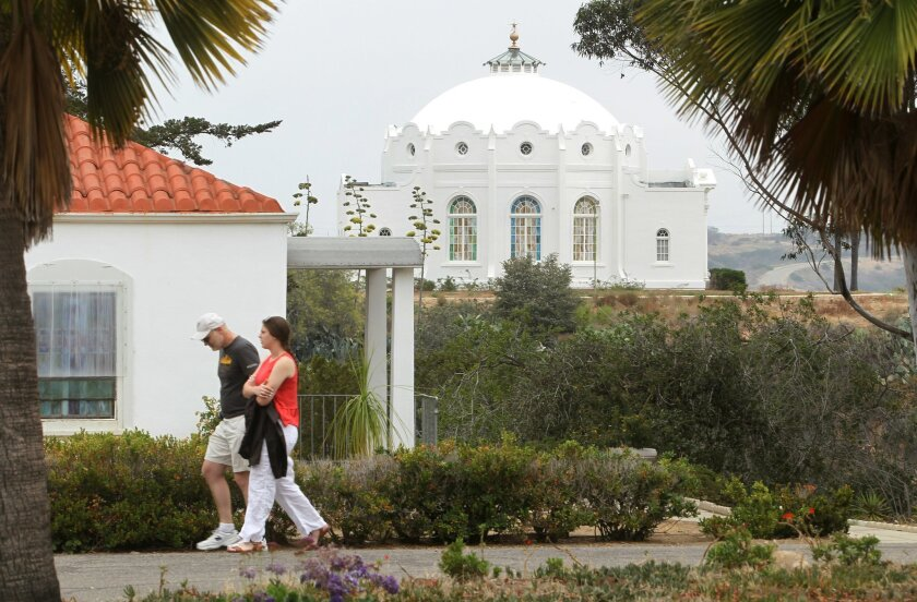 Visitors sroll past the Chapel on the Rosicrucian Fellowship grounds in Oceanside Friday. In the back can be seen the fellowship's distinctive Healing Temple. photo by Bill Wechter