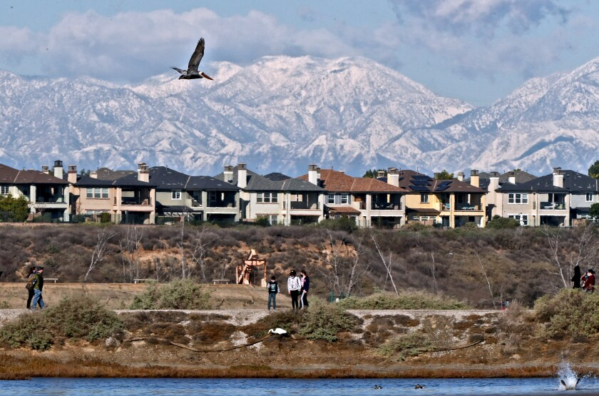A housing development in Huntington Beach overlooks Bolsa Chica Wetlands. The San Gabriel Mountains tower in the distance.