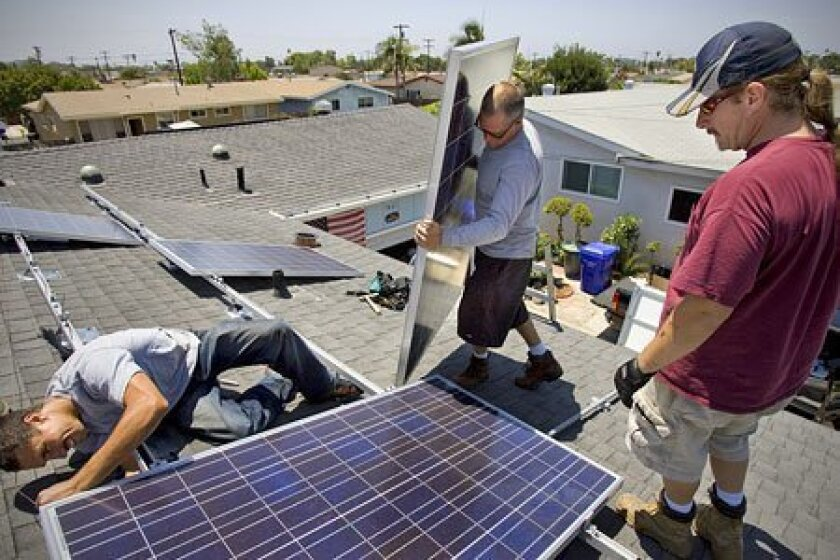 Solar West Electric workers Nathaniel Beeson (left) and Jason Ingram (right) installed solar panels as electrician Rhett Miller (middle) brought another panel into position in Clairemont.  (Nelvin C. Cepeda / Union-Tribune)