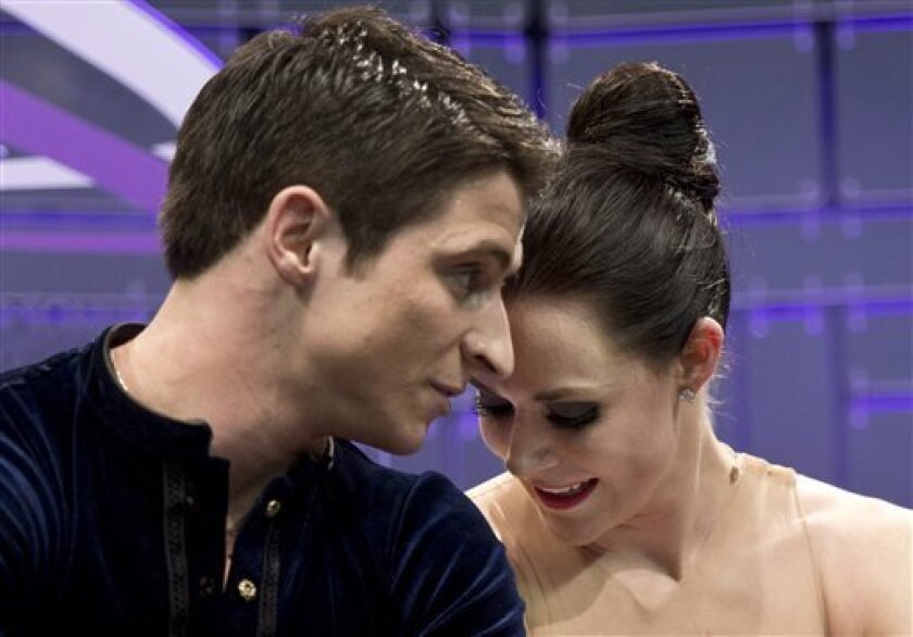 Tessa Virtue and Scott Moir, of Canada, react to their scores in the ice dance short program at the World Figure Skating Championships in London, Ontario, on Thursday, March 14, 2013. (AP Photo/The Canadian Press, Paul Chiasson)