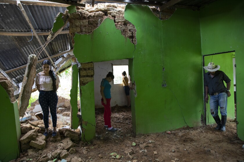"""From left, Marian Castron, 23; Maria Castron, 25; Jenny Castron, 19, and Omar Castron, 50, visit their home devastated by a landslide triggered by hurricanes Eta and Iota in the village of La Reina, Honduras, Friday, June 25, 2021. """"We plan to return, but it will be impossible,"""" says Omar. Home to about 1,000 people, the town in western Honduras was hit by two powerful hurricanes within three weeks, natural disasters made far worse by local deforestation and climate change. (AP Photo/Rodrigo Abd)"""