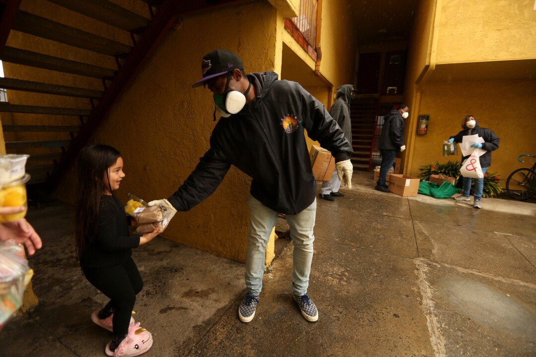 Ebay Williams, right, with the H.E.L.P.E.R. Foundation, gives a youngster and her family groceries at a low income government building in the Oakwood neighborhood in Venice.