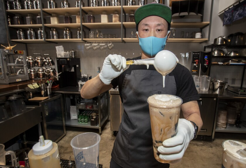A man drips the finishing touches on top of a large beverage